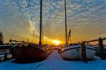 2 skutsjes ingevroren in ijs zonsondergang